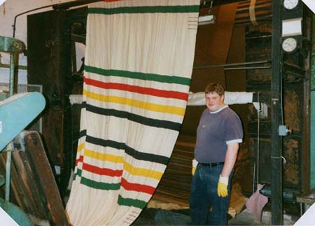 A member of Early's staff seeing a roll of point blankets through one of the final stages in the production process.